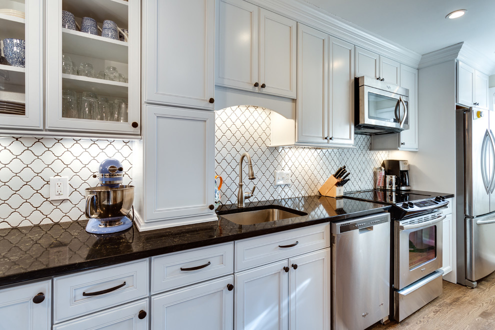 Inspiration for a mid-sized transitional l-shaped medium tone wood floor eat-in kitchen remodel in DC Metro with an undermount sink, flat-panel cabinets, white cabinets, quartz countertops, white backsplash, stainless steel appliances and a peninsula
