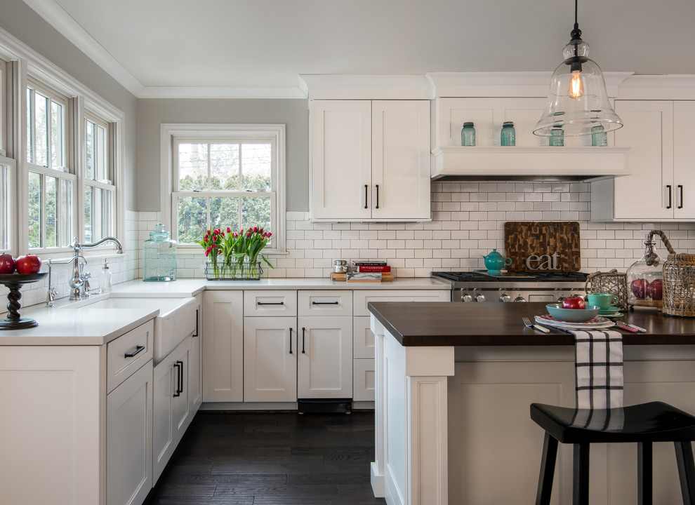 Inspiration for a large timeless l-shaped dark wood floor and brown floor kitchen remodel in Detroit with shaker cabinets, white cabinets, white backsplash, subway tile backsplash, stainless steel appliances, an island, a farmhouse sink, quartz countertops and white countertops