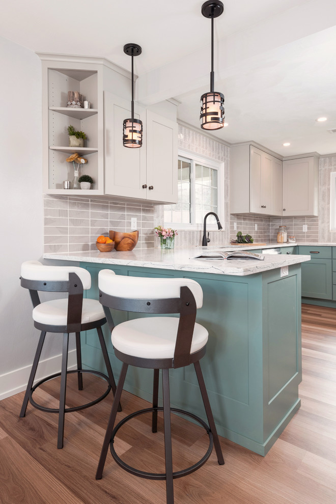 Example of a transitional u-shaped medium tone wood floor and brown floor enclosed kitchen design in Other with an undermount sink, shaker cabinets, turquoise cabinets, quartzite countertops, gray backsplash, porcelain backsplash, stainless steel appliances, a peninsula and white countertops
