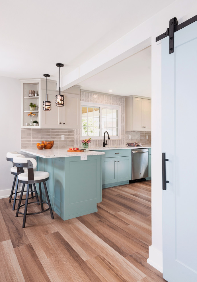 Inspiration for a transitional u-shaped medium tone wood floor and brown floor enclosed kitchen remodel in Other with an undermount sink, shaker cabinets, turquoise cabinets, quartzite countertops, gray backsplash, porcelain backsplash, stainless steel appliances, a peninsula and white countertops