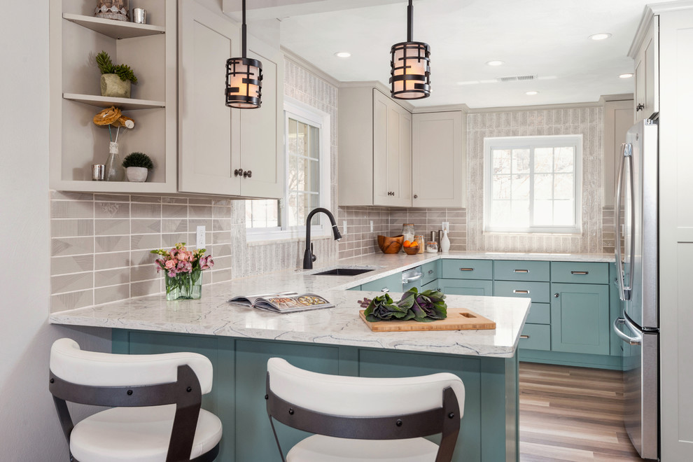 Inspiration for a transitional u-shaped medium tone wood floor and brown floor enclosed kitchen remodel in Other with an undermount sink, shaker cabinets, turquoise cabinets, gray backsplash, stainless steel appliances, a peninsula, white countertops, quartzite countertops and porcelain backsplash