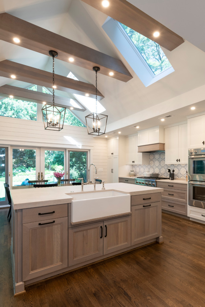 Inspiration for a large transitional l-shaped medium tone wood floor, brown floor and exposed beam kitchen remodel in DC Metro with a farmhouse sink, shaker cabinets, light wood cabinets, multicolored backsplash, stainless steel appliances and white countertops