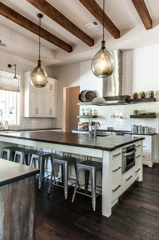 Example of a transitional u-shaped kitchen design in Austin with shaker cabinets, white cabinets, white backsplash, subway tile backsplash, stainless steel appliances and wood countertops