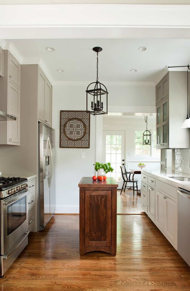 Example of a transitional galley kitchen design in Atlanta with an undermount sink, recessed-panel cabinets, gray cabinets, granite countertops, white backsplash, subway tile backsplash and stainless steel appliances