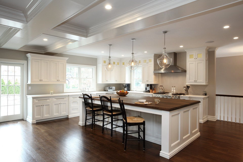 Eat-in kitchen - large transitional l-shaped medium tone wood floor eat-in kitchen idea in New York with recessed-panel cabinets, white cabinets, wood countertops, stainless steel appliances, an island, a farmhouse sink and gray backsplash
