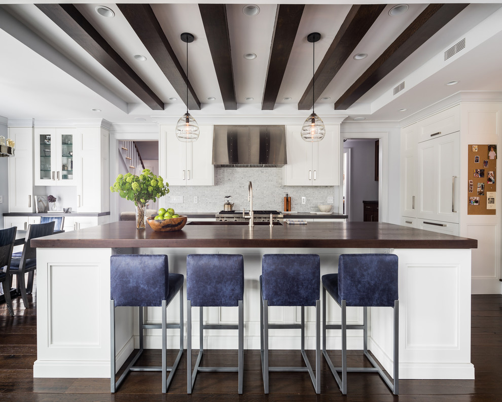 Eat-in kitchen - mid-sized transitional galley dark wood floor eat-in kitchen idea in Boston with recessed-panel cabinets, white cabinets, wood countertops, gray backsplash, stainless steel appliances, an island, an undermount sink and stone tile backsplash