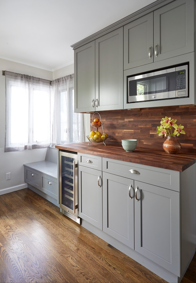 Example of a mid-sized transitional brown floor and dark wood floor kitchen design in San Francisco with shaker cabinets, gray cabinets, wood countertops, brown backsplash, stainless steel appliances, brown countertops and wood backsplash