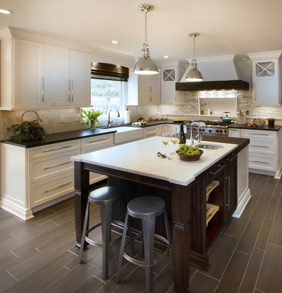 Inspiration for a transitional kitchen remodel in New York with a farmhouse sink, shaker cabinets, white cabinets, marble countertops, white backsplash, stone tile backsplash and stainless steel appliances