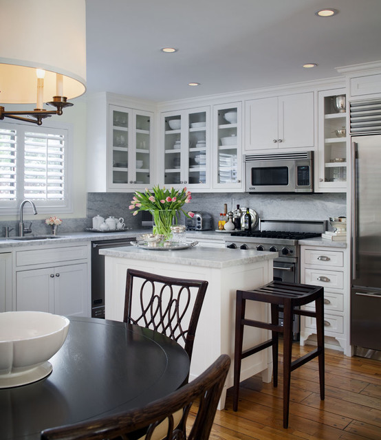 Eat-in kitchen - small traditional l-shaped medium tone wood floor eat-in kitchen idea in Los Angeles with stainless steel appliances, glass-front cabinets, white cabinets, an undermount sink, stone slab backsplash, marble countertops, an island and gray backsplash