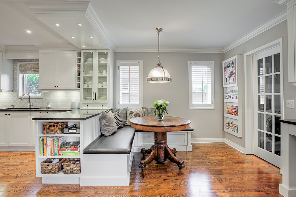 Example of a transitional medium tone wood floor eat-in kitchen design in Toronto with an undermount sink, recessed-panel cabinets and white appliances