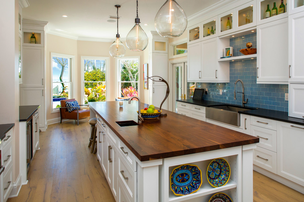 Large transitional galley medium tone wood floor and brown floor eat-in kitchen photo in Tampa with a farmhouse sink, recessed-panel cabinets, white cabinets, blue backsplash, stainless steel appliances, an island, wood countertops, subway tile backsplash and black countertops