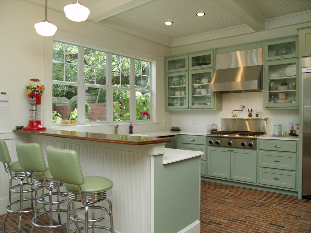 Example of a classic u-shaped kitchen design in Austin with glass-front cabinets, green cabinets, white backsplash, stainless steel appliances and subway tile backsplash