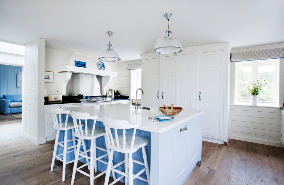 Beach style u-shaped medium tone wood floor and brown floor kitchen photo in Wiltshire with a farmhouse sink, recessed-panel cabinets, white cabinets, paneled appliances and an island