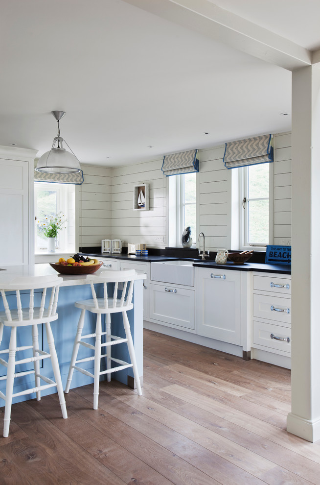 Beach style medium tone wood floor kitchen photo in Wiltshire with a farmhouse sink, recessed-panel cabinets, white cabinets, paneled appliances, quartz countertops and an island