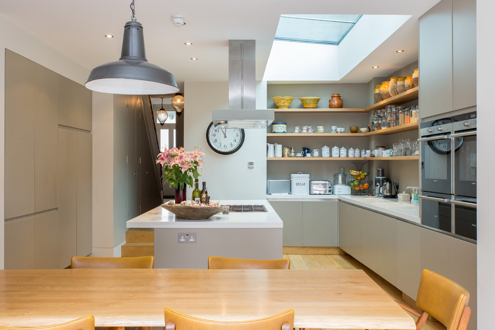 Example of a large trendy light wood floor eat-in kitchen design in London with flat-panel cabinets, gray cabinets and an island