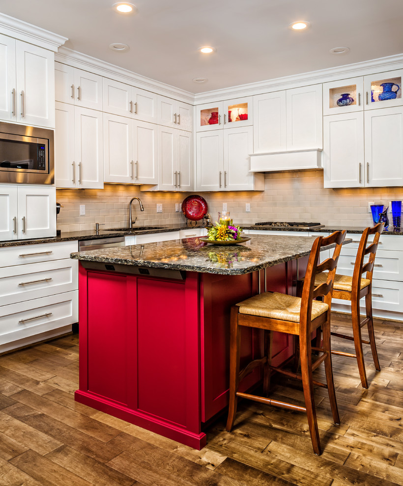 Example of a large transitional l-shaped medium tone wood floor and brown floor enclosed kitchen design in Detroit with an undermount sink, shaker cabinets, white cabinets, quartz countertops, gray backsplash, ceramic backsplash, stainless steel appliances and an island