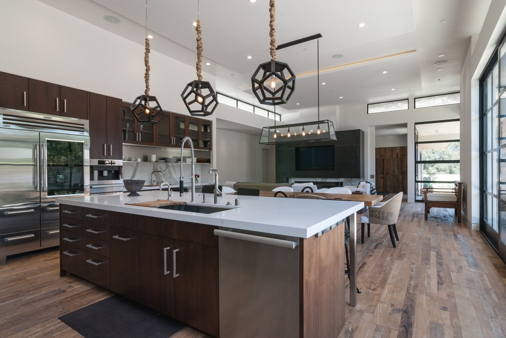 Large minimalist l-shaped light wood floor open concept kitchen photo in San Diego with an undermount sink, flat-panel cabinets, dark wood cabinets, white backsplash, stainless steel appliances, stone slab backsplash, quartzite countertops and an island