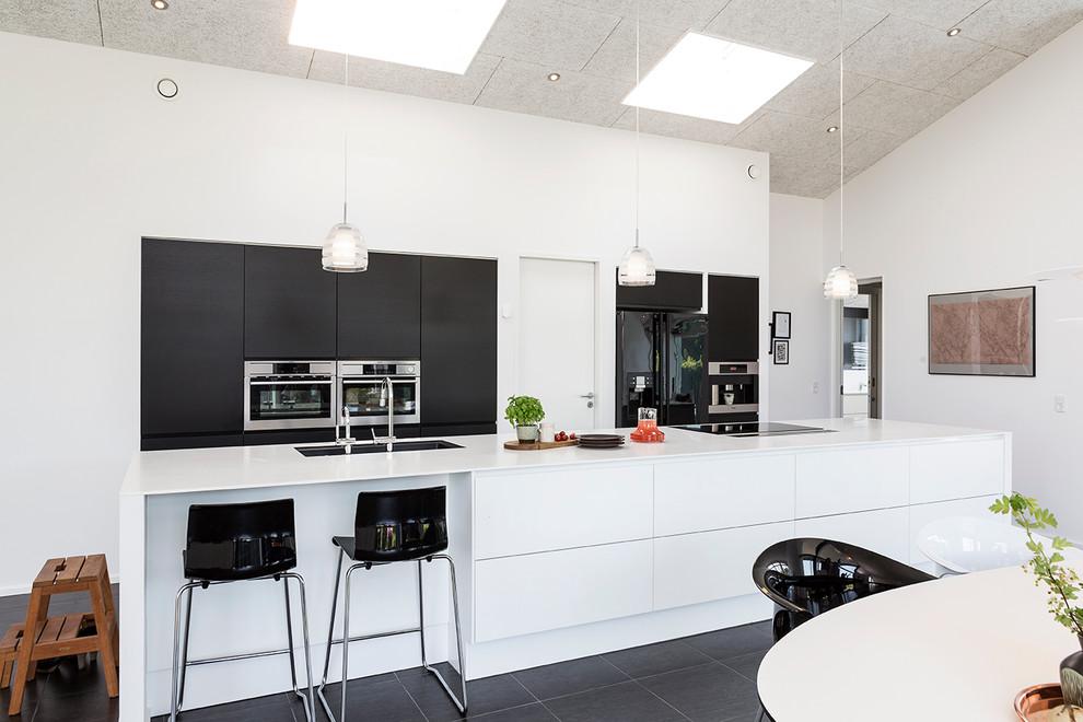 Стильный дизайн: большая параллельная кухня в современном стиле с обеденным столом, островом, плоскими фасадами, черными фасадами, врезной раковиной, полом из сланца и техникой из нержавеющей стали - последний тренд