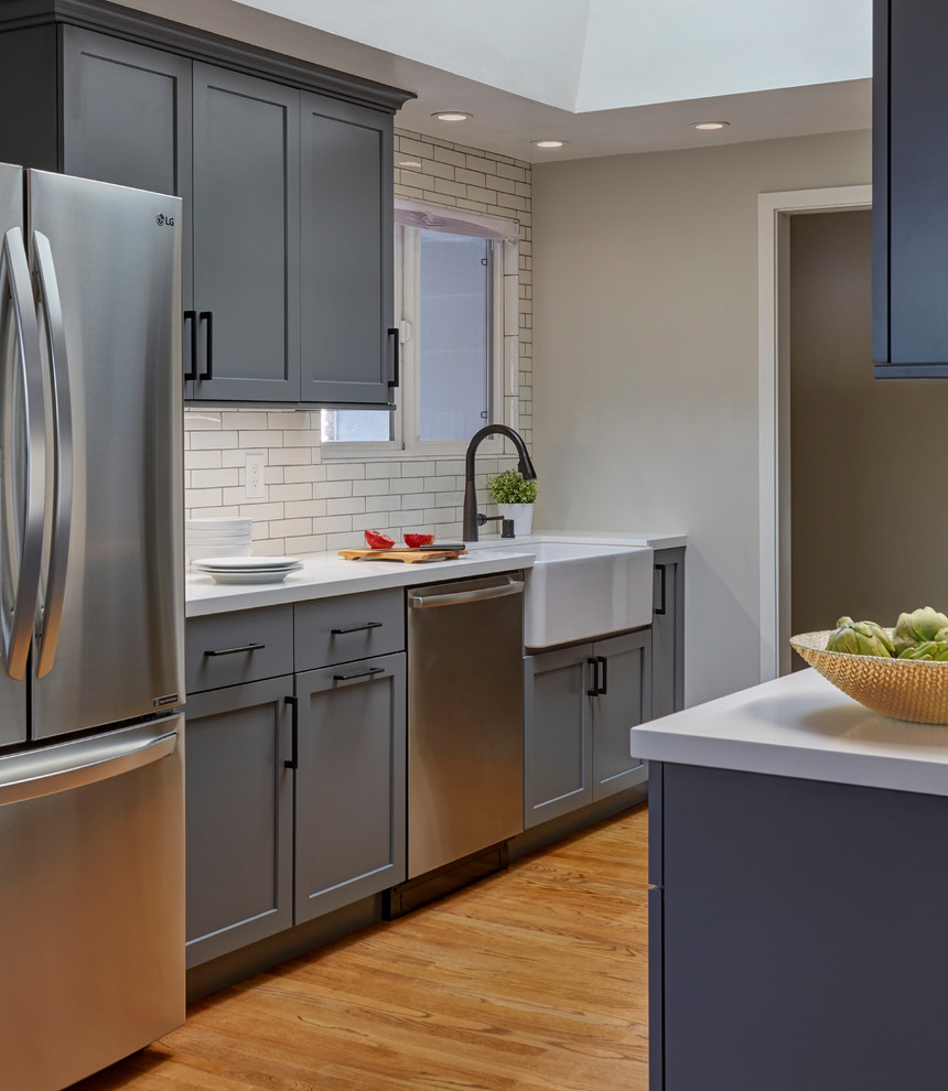 Inspiration for a mid-sized transitional galley eat-in kitchen remodel in San Francisco with a farmhouse sink, shaker cabinets, gray cabinets, quartzite countertops, white backsplash, subway tile backsplash, stainless steel appliances, an island and white countertops