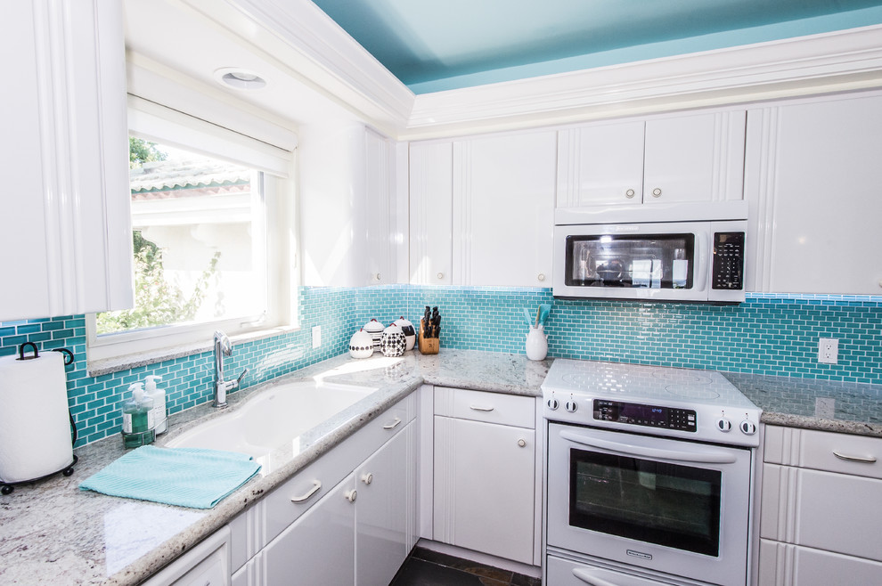 Mid-sized beach style single-wall eat-in kitchen photo in Miami with an undermount sink, flat-panel cabinets, white cabinets, granite countertops, blue backsplash, glass tile backsplash, white appliances and a peninsula