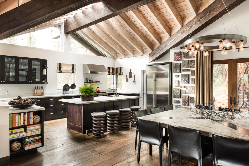 Eat-in kitchen - large industrial l-shaped medium tone wood floor eat-in kitchen idea in Sacramento with glass-front cabinets, black cabinets, stainless steel appliances, an island, an undermount sink, quartz countertops and white backsplash