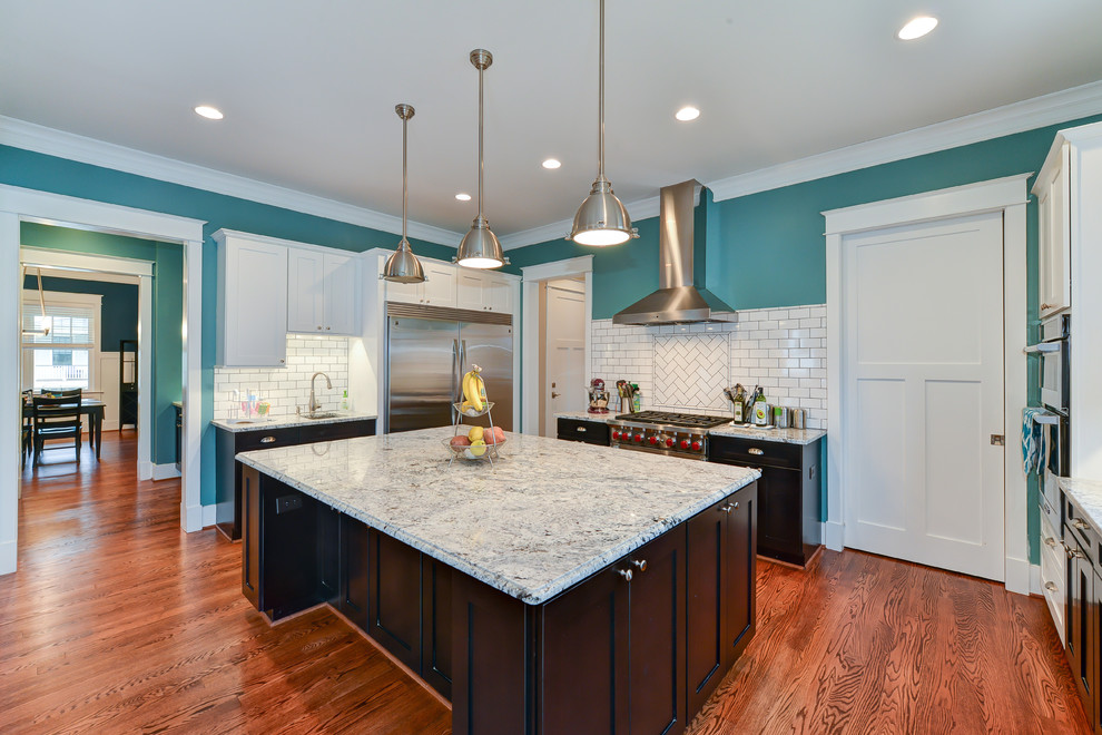 Inspiration for a large craftsman u-shaped medium tone wood floor eat-in kitchen remodel with an undermount sink, recessed-panel cabinets, dark wood cabinets, quartzite countertops, white backsplash, ceramic backsplash, stainless steel appliances and an island