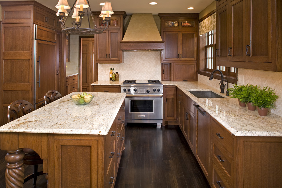 Example of a classic kitchen design in Minneapolis with recessed-panel cabinets, medium tone wood cabinets, beige backsplash and paneled appliances
