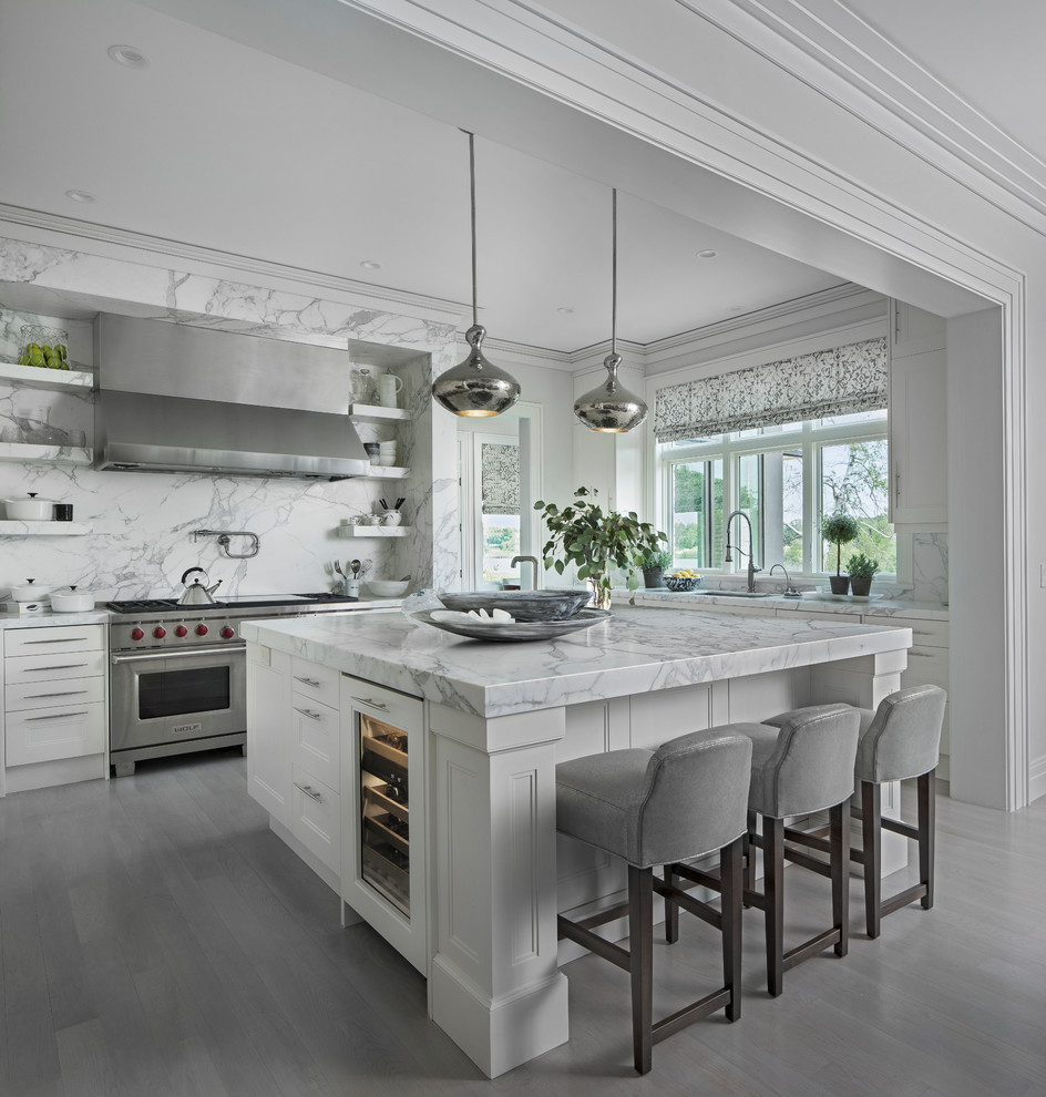 Example of a transitional l-shaped gray floor kitchen design in Detroit with recessed-panel cabinets, white cabinets, gray backsplash, stainless steel appliances, an island and gray countertops