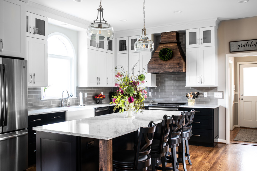 Enclosed kitchen - mid-sized farmhouse l-shaped medium tone wood floor and brown floor enclosed kitchen idea in Charlotte with a farmhouse sink, shaker cabinets, quartz countertops, gray backsplash, subway tile backsplash, stainless steel appliances, an island, white countertops and white cabinets