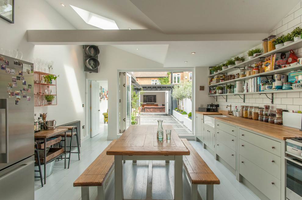 Example of a cottage light wood floor kitchen design in London with a farmhouse sink, flat-panel cabinets, green cabinets, white backsplash, subway tile backsplash and stainless steel appliances