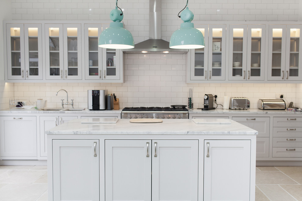 Inspiration for a transitional kitchen remodel in Surrey with a double-bowl sink, glass-front cabinets, white cabinets, white backsplash, subway tile backsplash, stainless steel appliances and an island