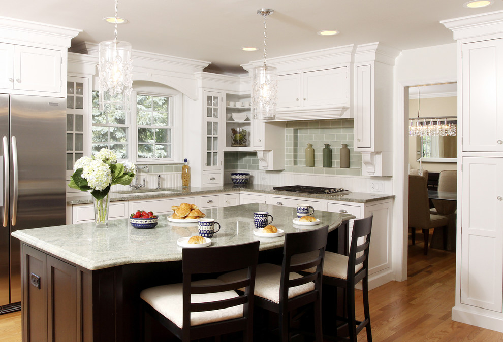 Enclosed kitchen - large traditional l-shaped medium tone wood floor enclosed kitchen idea in Chicago with an undermount sink, shaker cabinets, white cabinets, granite countertops, green backsplash, subway tile backsplash, stainless steel appliances and an island