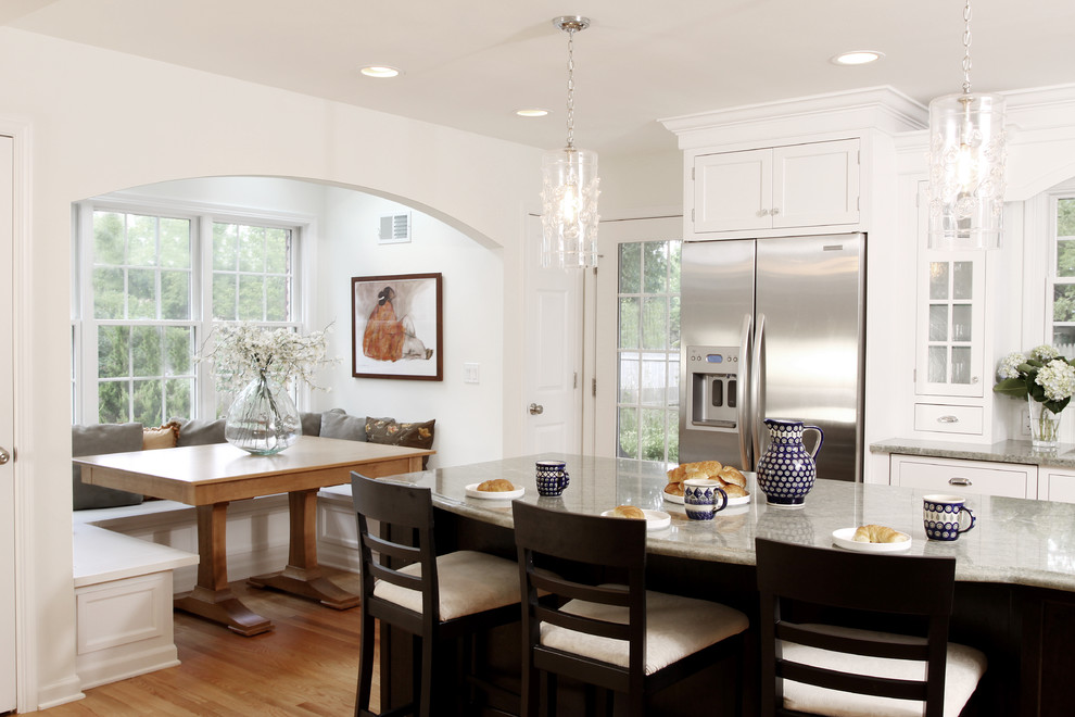 Large elegant medium tone wood floor eat-in kitchen photo in Chicago with shaker cabinets, white cabinets, stainless steel appliances, granite countertops and an island