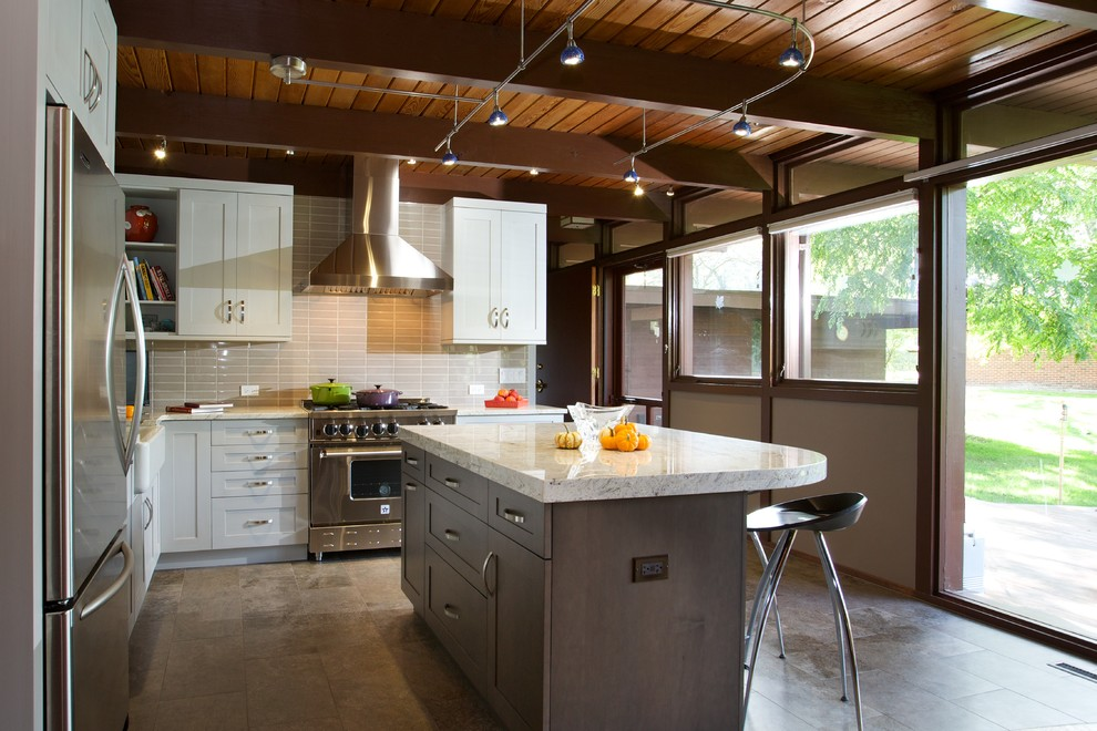 Example of a mid-sized trendy l-shaped travertine floor enclosed kitchen design in Chicago with a farmhouse sink, shaker cabinets, white cabinets, stainless steel appliances, an island, marble countertops, beige backsplash and porcelain backsplash