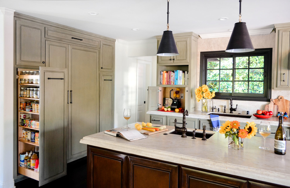 Example of a large tuscan l-shaped dark wood floor and brown floor open concept kitchen design in Los Angeles with an undermount sink, raised-panel cabinets, green cabinets, quartzite countertops, beige backsplash, stone slab backsplash, paneled appliances, an island and beige countertops