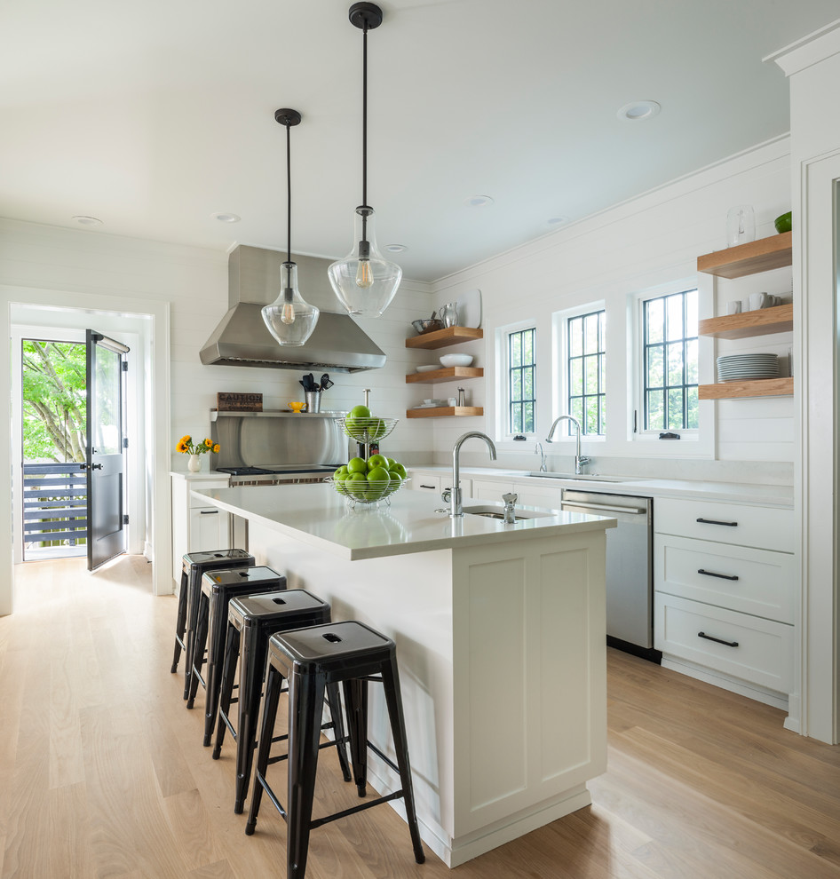 Example of a mid-sized transitional u-shaped light wood floor and beige floor open concept kitchen design in Seattle with an undermount sink, shaker cabinets, white cabinets, metallic backsplash, stainless steel appliances, an island and quartzite countertops