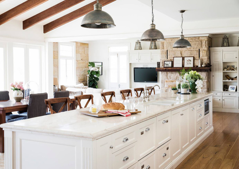 Inspiration for a farmhouse galley medium tone wood floor open concept kitchen remodel in Sydney with a double-bowl sink, recessed-panel cabinets, white cabinets and an island