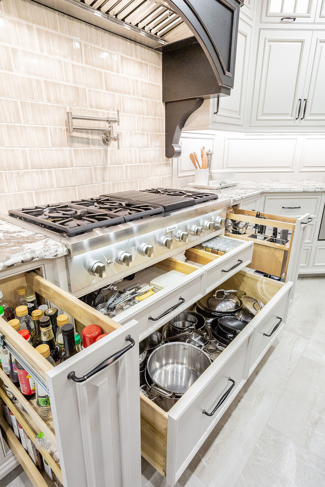 Example of a large transitional porcelain floor and beige floor kitchen design in Other with a farmhouse sink, beaded inset cabinets, gray cabinets, granite countertops, porcelain backsplash, stainless steel appliances, an island and beige countertops