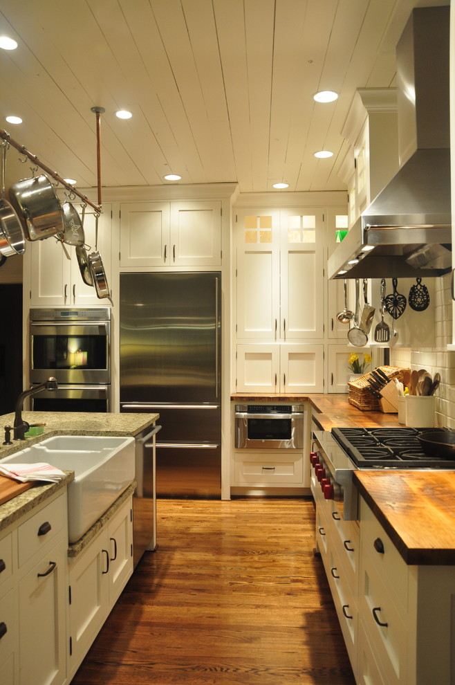 Example of a mid-sized country galley medium tone wood floor enclosed kitchen design in Louisville with a farmhouse sink, stainless steel appliances, shaker cabinets, wood countertops, white cabinets, white backsplash, ceramic backsplash and an island