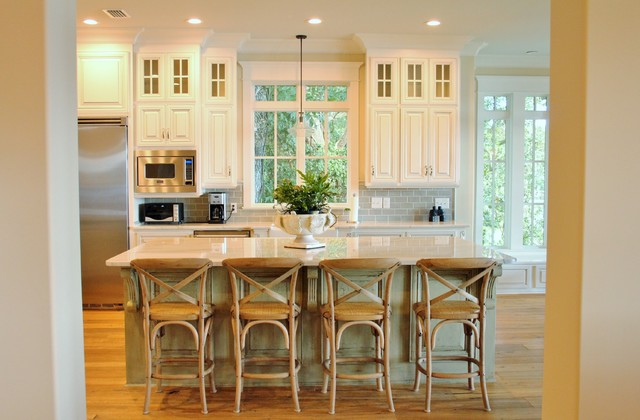 Inspiration for an u-shaped light wood floor eat-in kitchen remodel in Other with a farmhouse sink, raised-panel cabinets, white cabinets, marble countertops, white backsplash, porcelain backsplash, stainless steel appliances and an island