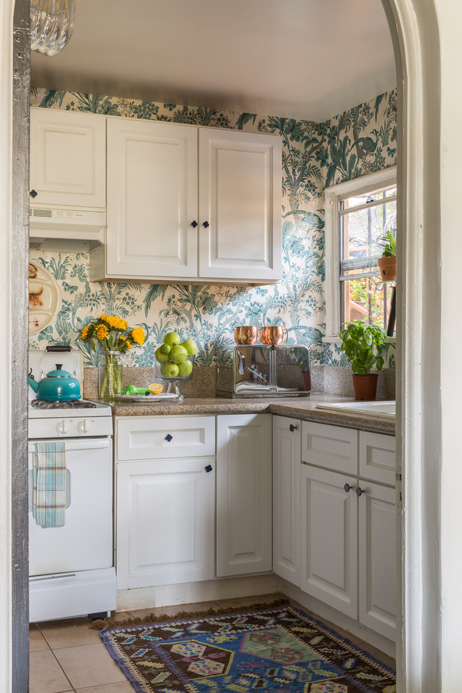 Enclosed kitchen - small traditional l-shaped beige floor enclosed kitchen idea in Los Angeles with a drop-in sink, raised-panel cabinets, white cabinets, multicolored backsplash, white appliances, no island and brown countertops