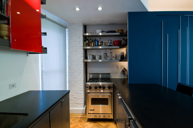 Example of a minimalist open concept kitchen design in New York with stainless steel appliances, an undermount sink, flat-panel cabinets and blue cabinets