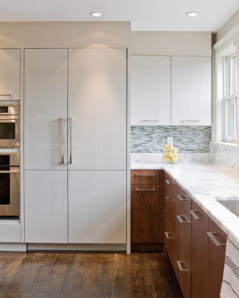 Kitchen - contemporary kitchen idea in Boston with paneled appliances, marble countertops, flat-panel cabinets, white cabinets, an undermount sink, matchstick tile backsplash and gray backsplash
