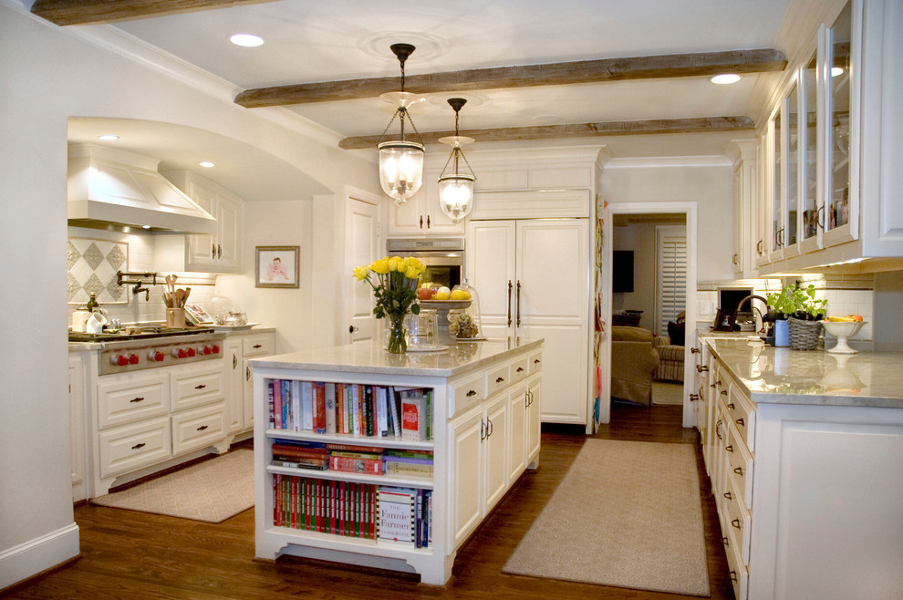 Kitchen - traditional kitchen idea in Dallas with glass-front cabinets, marble countertops, white cabinets and paneled appliances