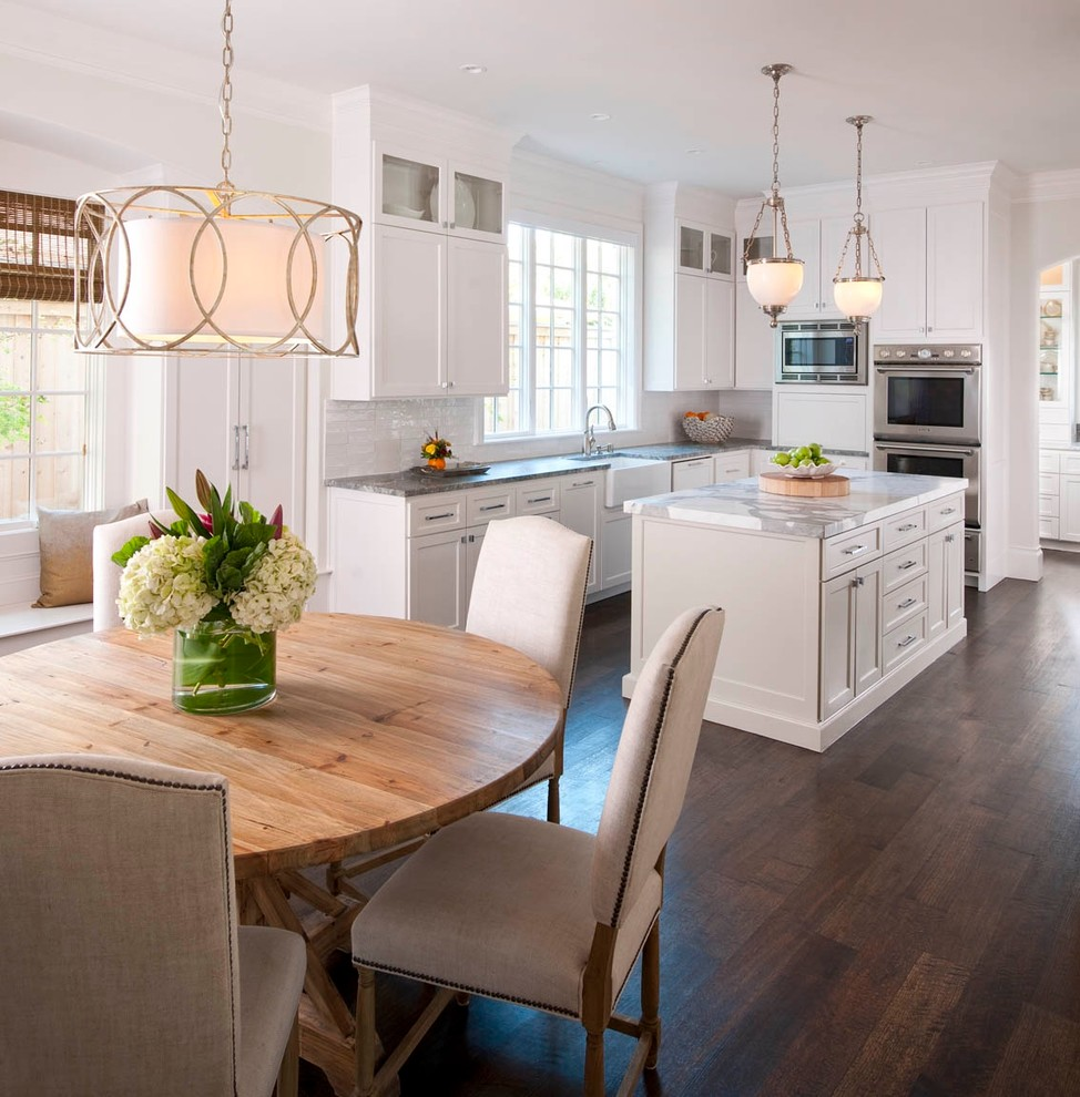 Eat-in kitchen - traditional eat-in kitchen idea in Dallas with a farmhouse sink, recessed-panel cabinets, white cabinets, white backsplash, marble countertops and gray countertops
