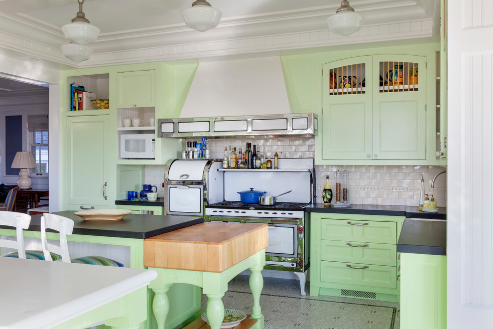 Example of a large beach style u-shaped linoleum floor and gray floor enclosed kitchen design in Boston with shaker cabinets, green cabinets, beige backsplash, subway tile backsplash, white appliances, an island and solid surface countertops