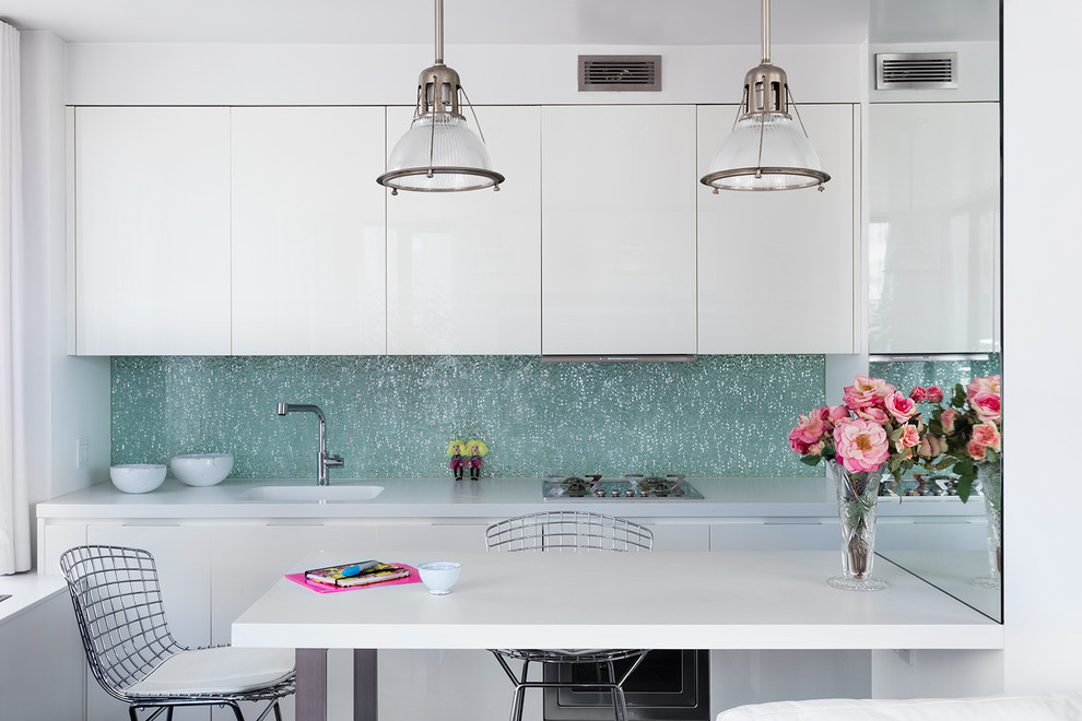 Small trendy single-wall eat-in kitchen photo in New York with white cabinets, blue backsplash, a peninsula, white countertops, an integrated sink and flat-panel cabinets