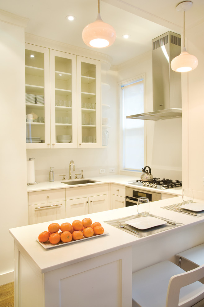 Small trendy u-shaped light wood floor and brown floor eat-in kitchen photo in New York with an undermount sink, shaker cabinets, white cabinets, quartz countertops, stainless steel appliances and a peninsula