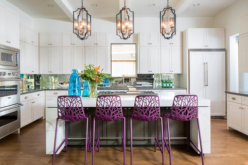 Ultra Violet purple bar stools on a kitchen island in a White painted kitchen design make a color pop.
