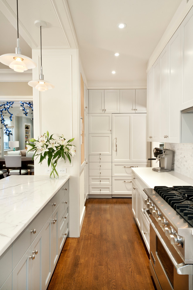 Small transitional u-shaped medium tone wood floor and brown floor open concept kitchen photo in New York with gray backsplash, paneled appliances, an undermount sink, marble countertops, stone tile backsplash, a peninsula, shaker cabinets and white cabinets